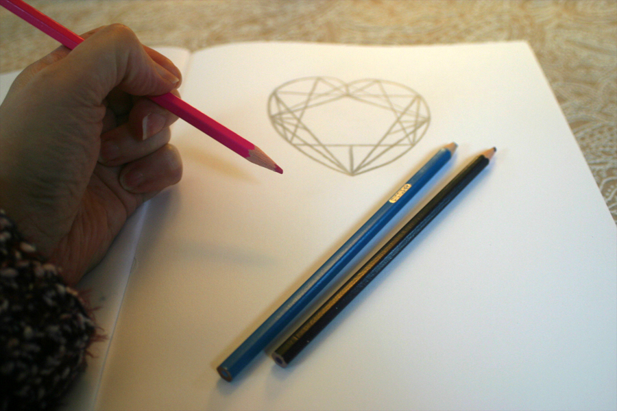 sketching crystal heart logo in book.